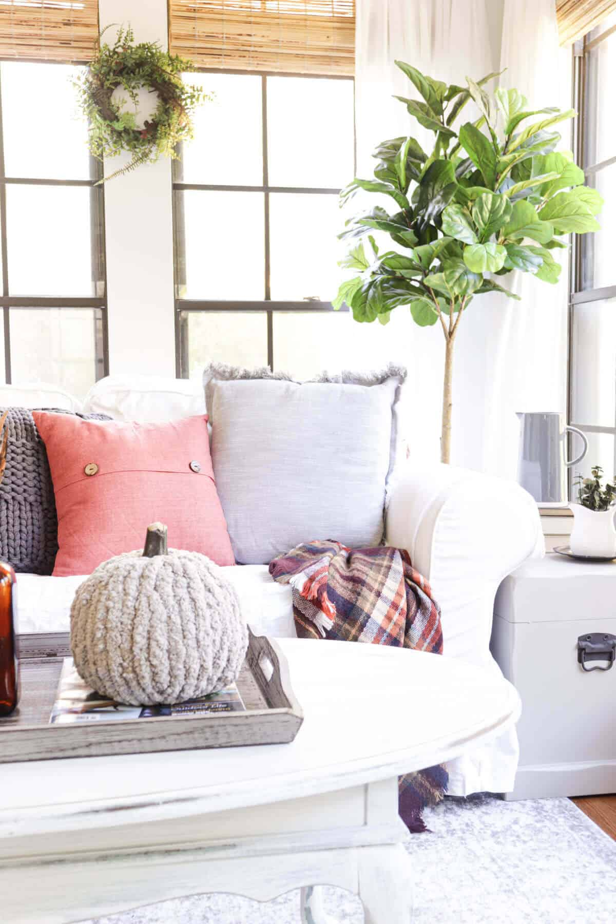 white love seat with gray and orange pillows behind a coffee table with a chunky knit yarn covered pumpkin