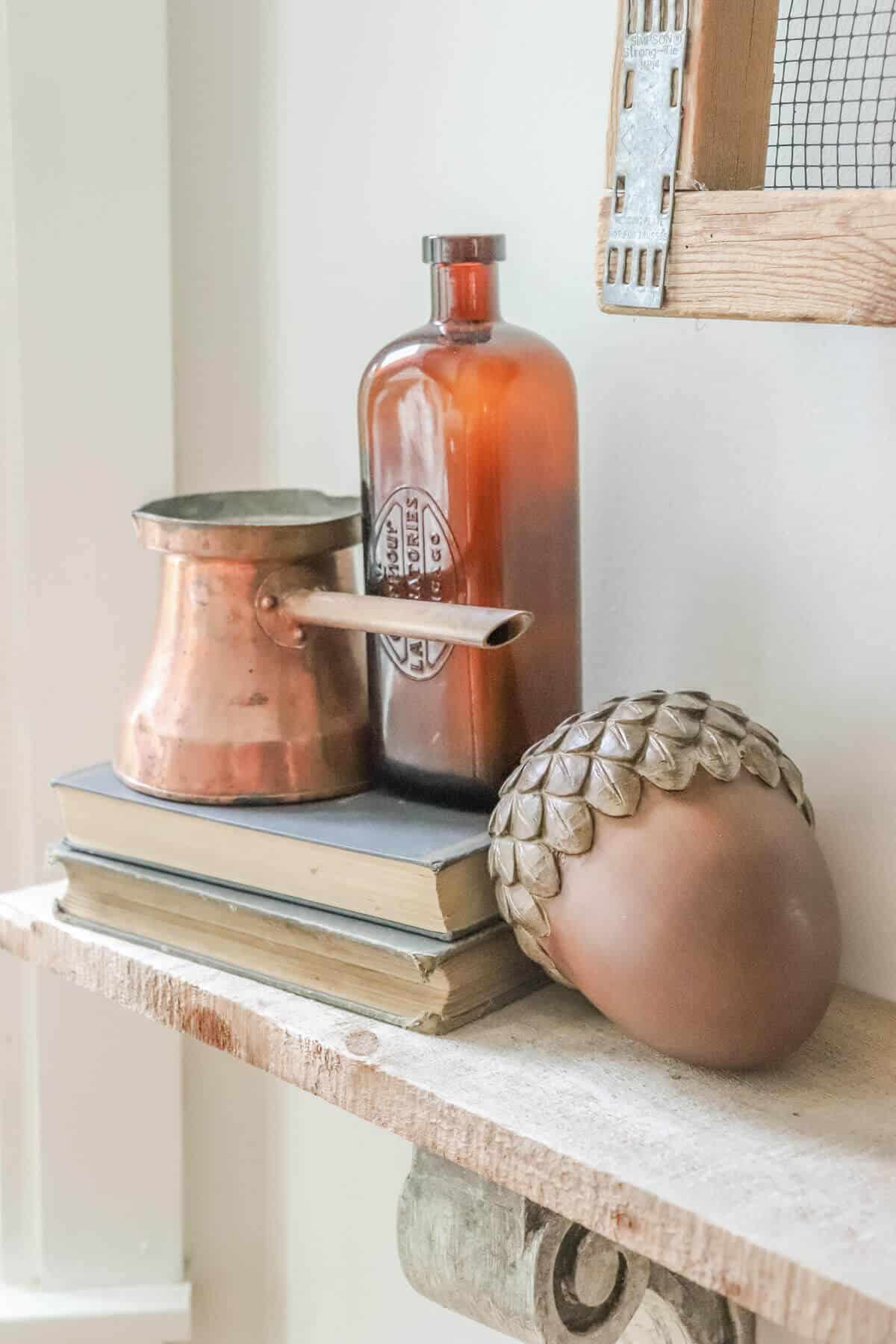 shelf with green books, copper melting bowl, wooden acorn and amber brown bottle