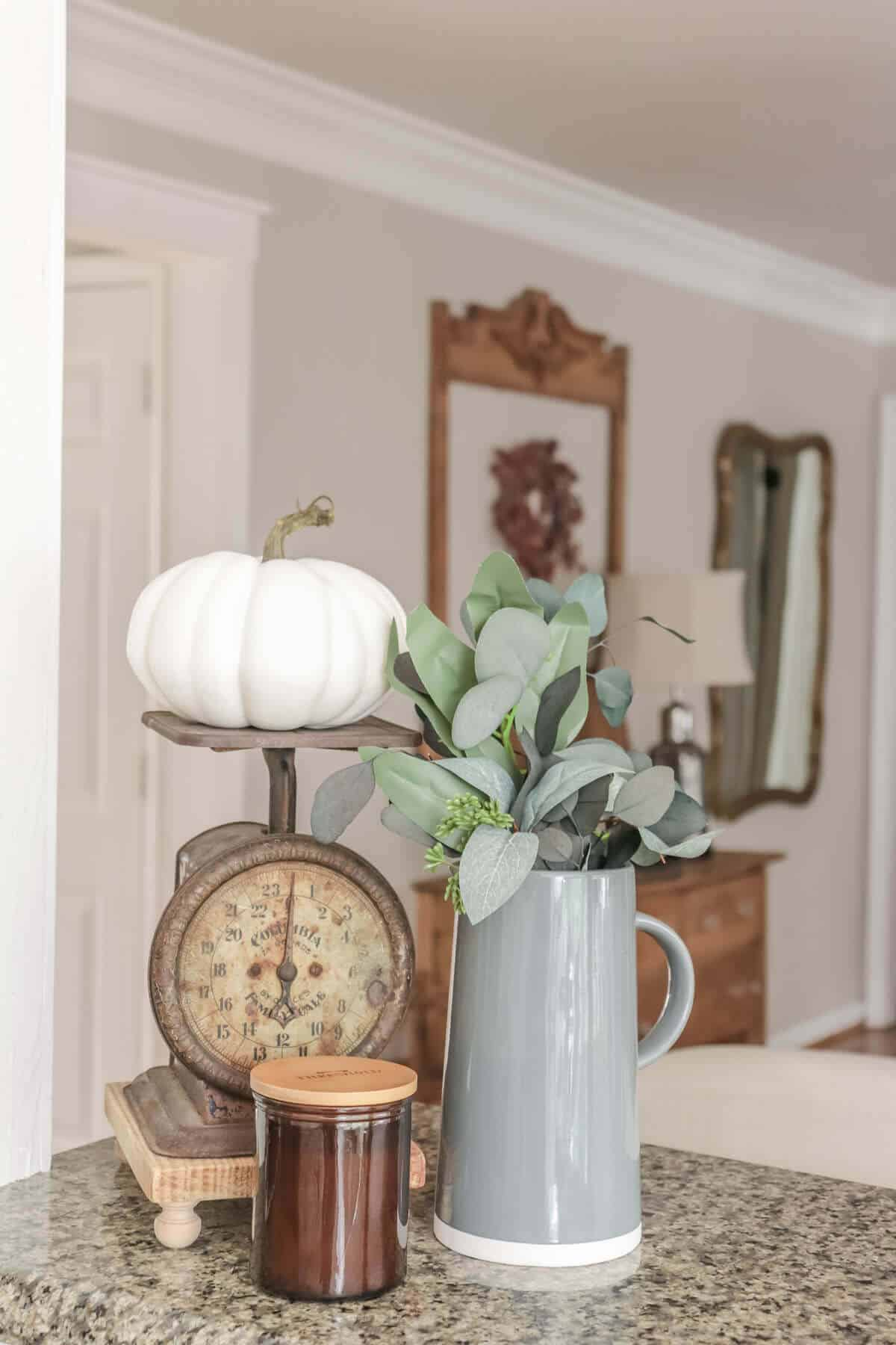 rusty vintage kitchen scale decorated for fall with a white pumpkin, gray pitcher filled with dried eucalyptus and a small candle