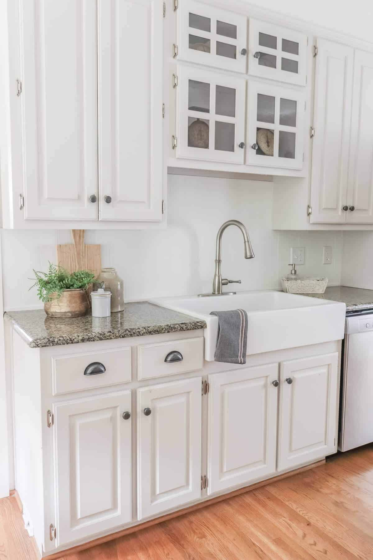 Light beige kitchen cabinets with granite counters, apron front sink and stone crockery