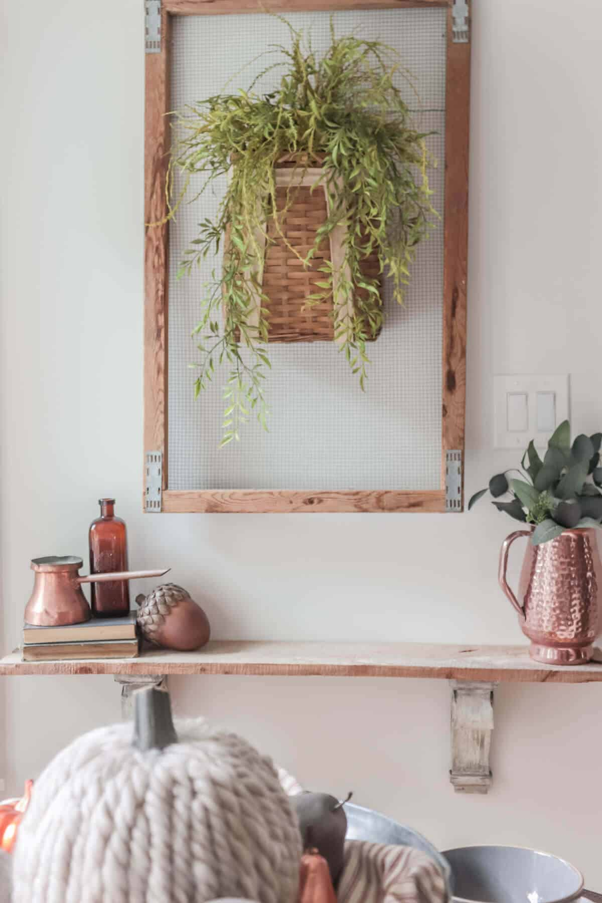 Tulip basket hanging on a wall with greenery trailing down over a small wall shelf decorated for fall