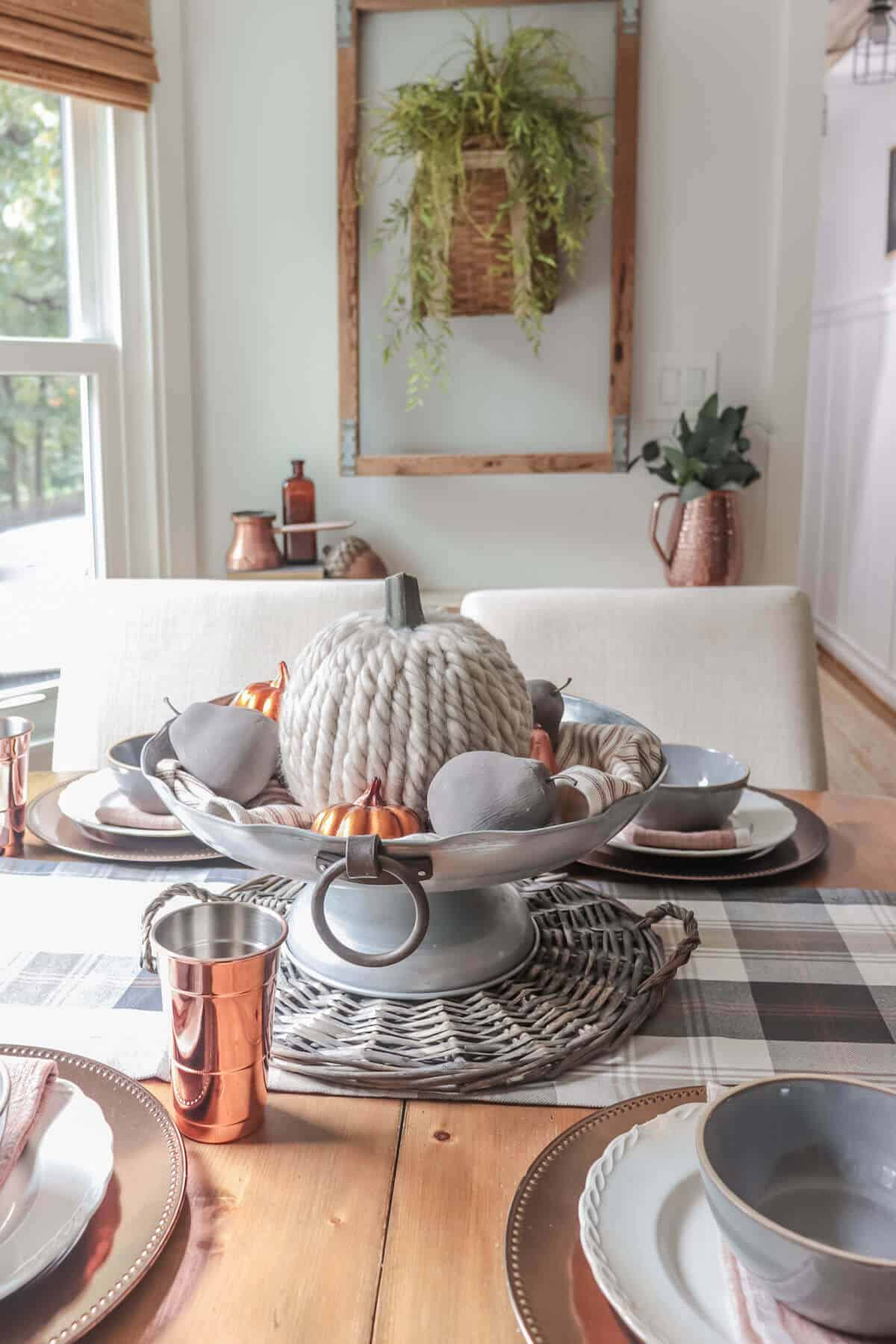 metal centerpiece bowl filled with orange and white striped towel, gray cement pears, a yarn covered pumpkin and copper pumpkins