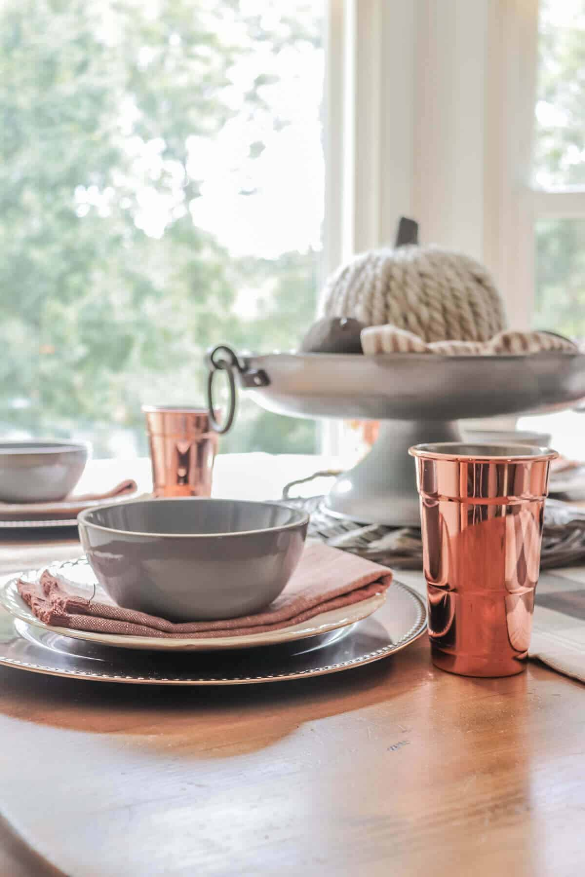 Place setting with copper charger and glass, gray bowl and pumpkin orange fringe napkin