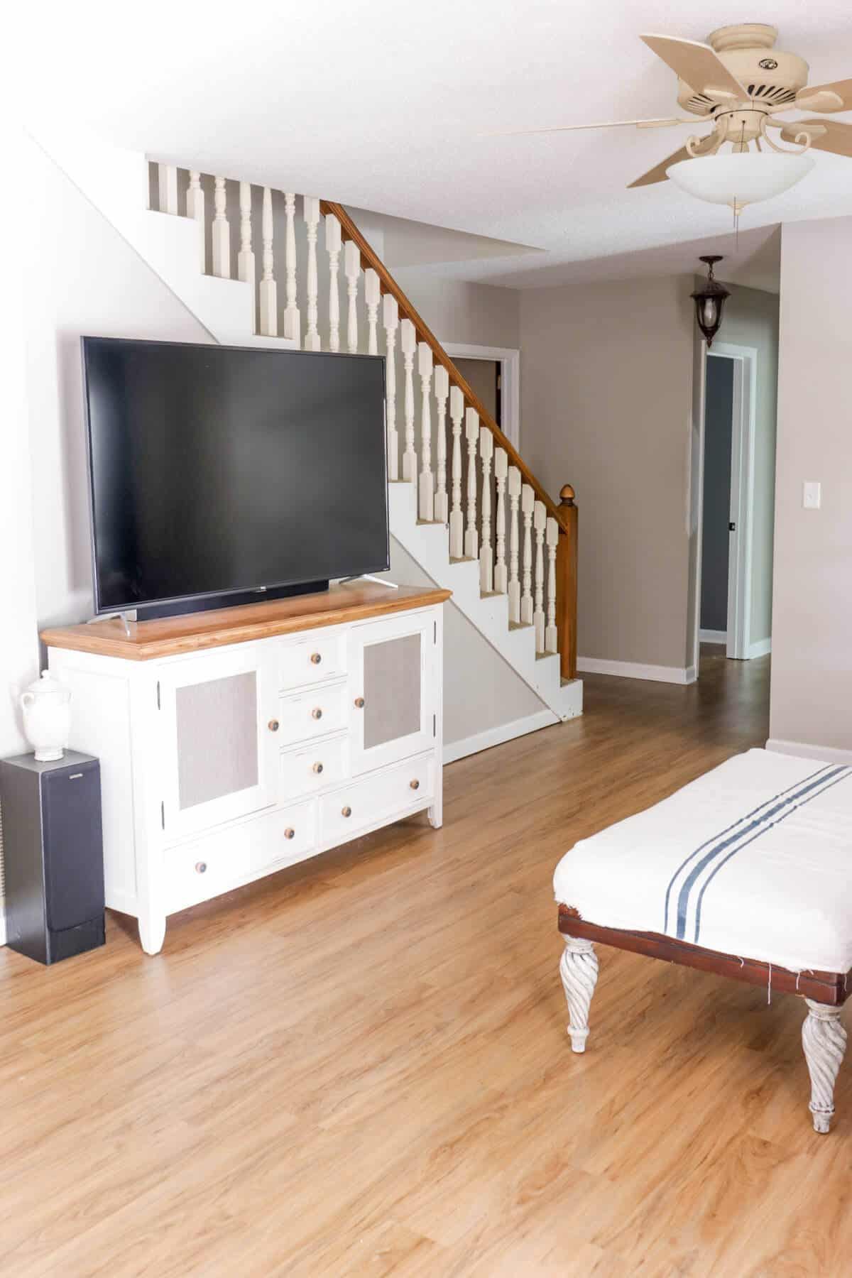 white entertainment center with black TV in a basement family room with popcorn ceilings and beige ceiling fan