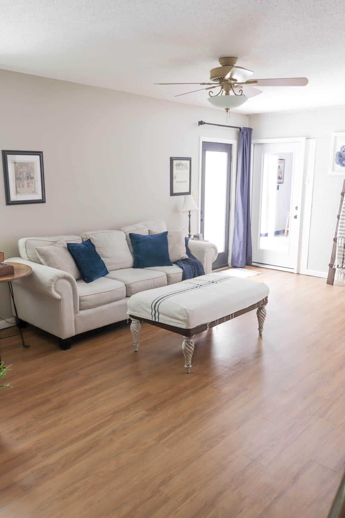 basement family room with rooms to go beige couch with blue accent pillows and curtains