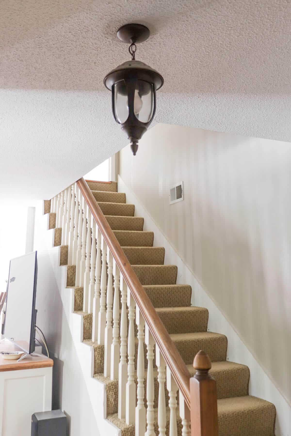 dated stairway with popcorn coated ceiling and old hanging pendant light