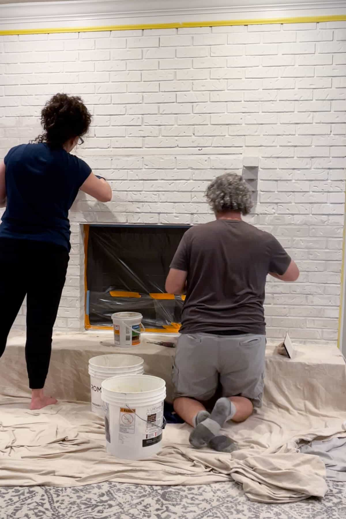 husband and wife working on fireplace filling recessed mortar joints