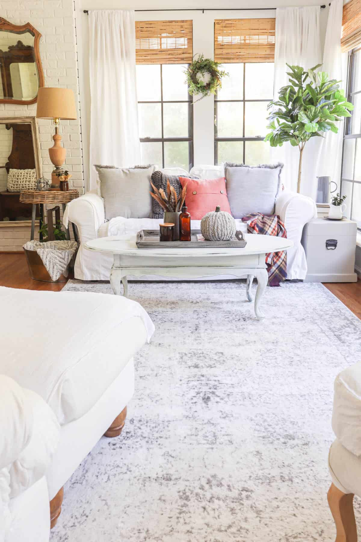 sun room with white sofa and gray rug. There are gray and orange pillows on the sofa and a coffee table with fall decor