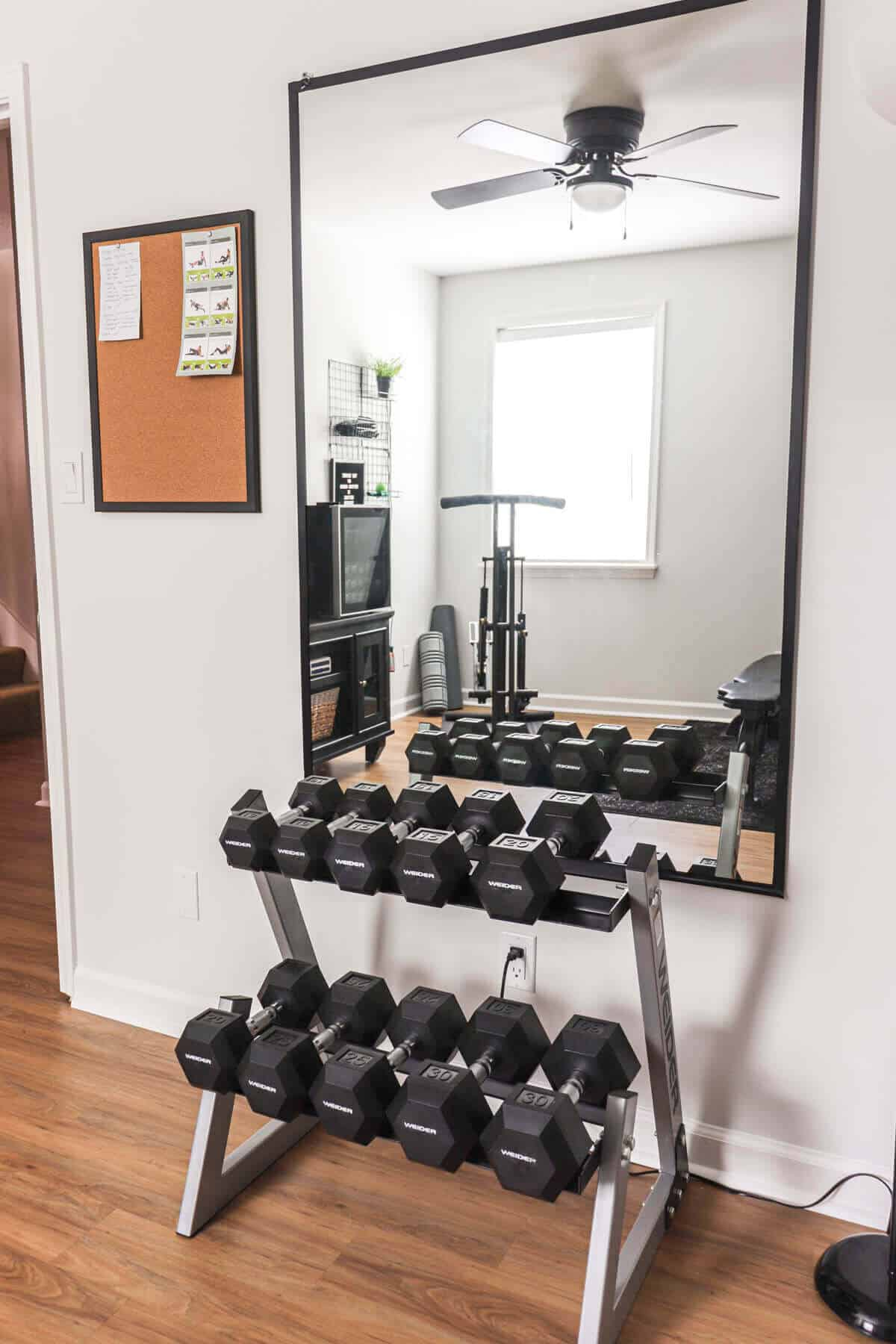 free weight rack in front of a mirror