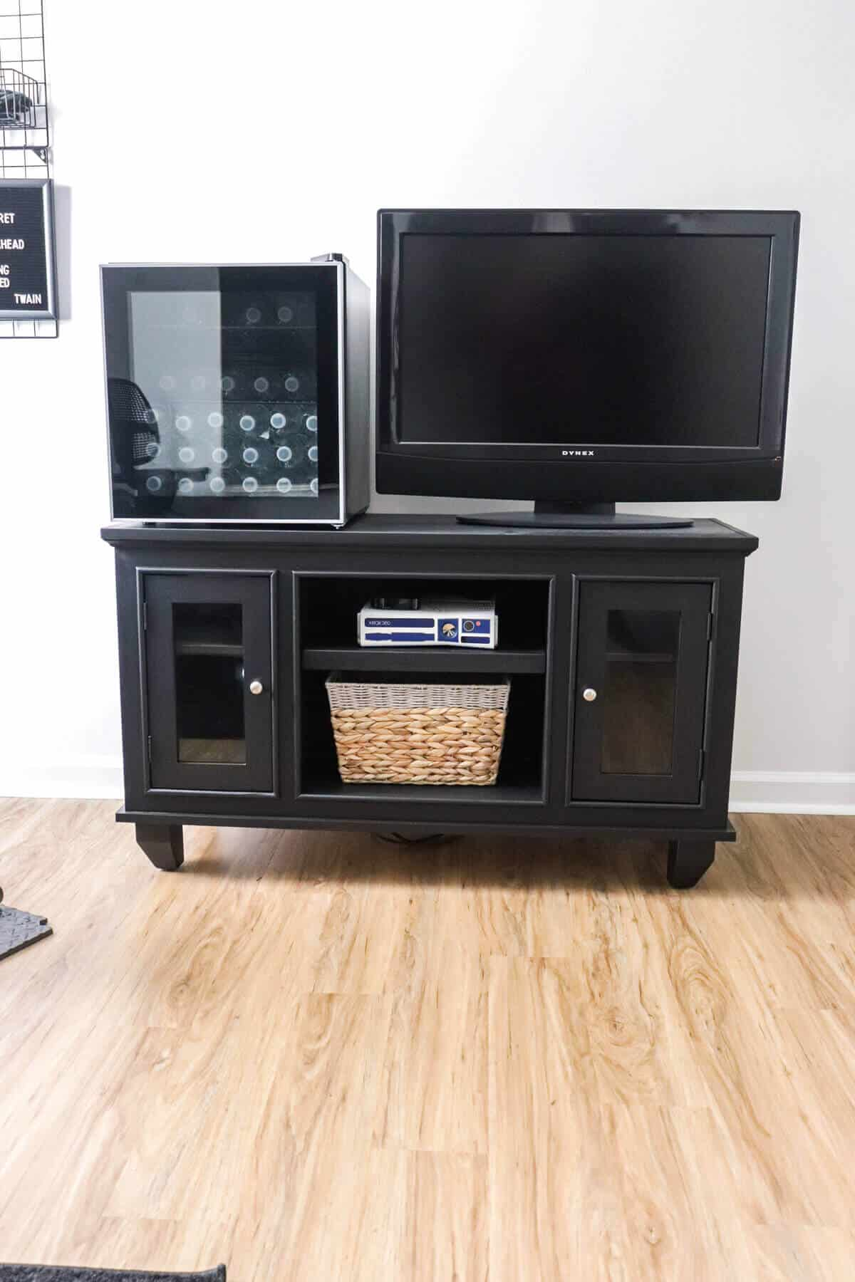 Black painted entertainment center for home gym with mini fridge filled with water