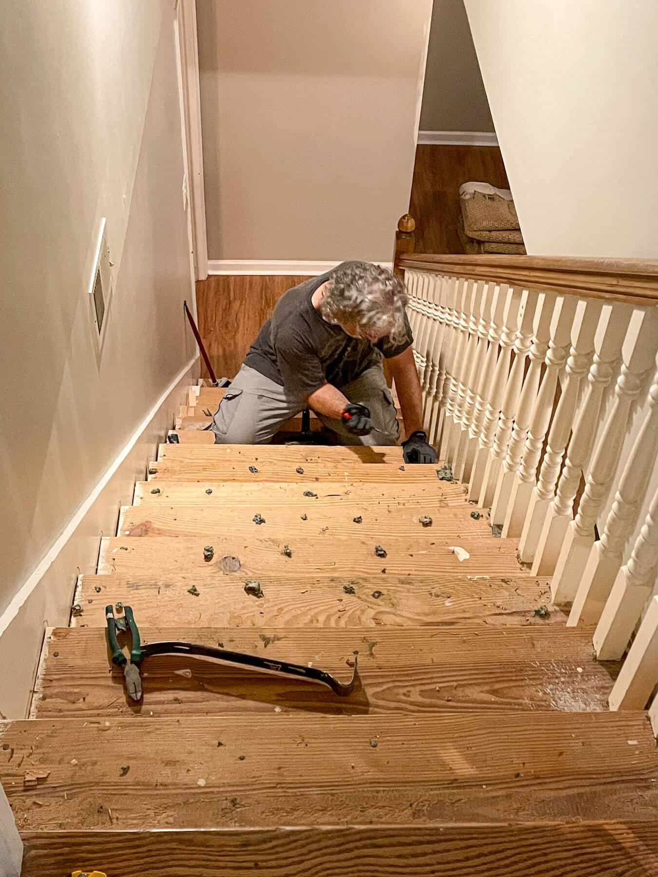 man removing carpeting staples from basement stairs