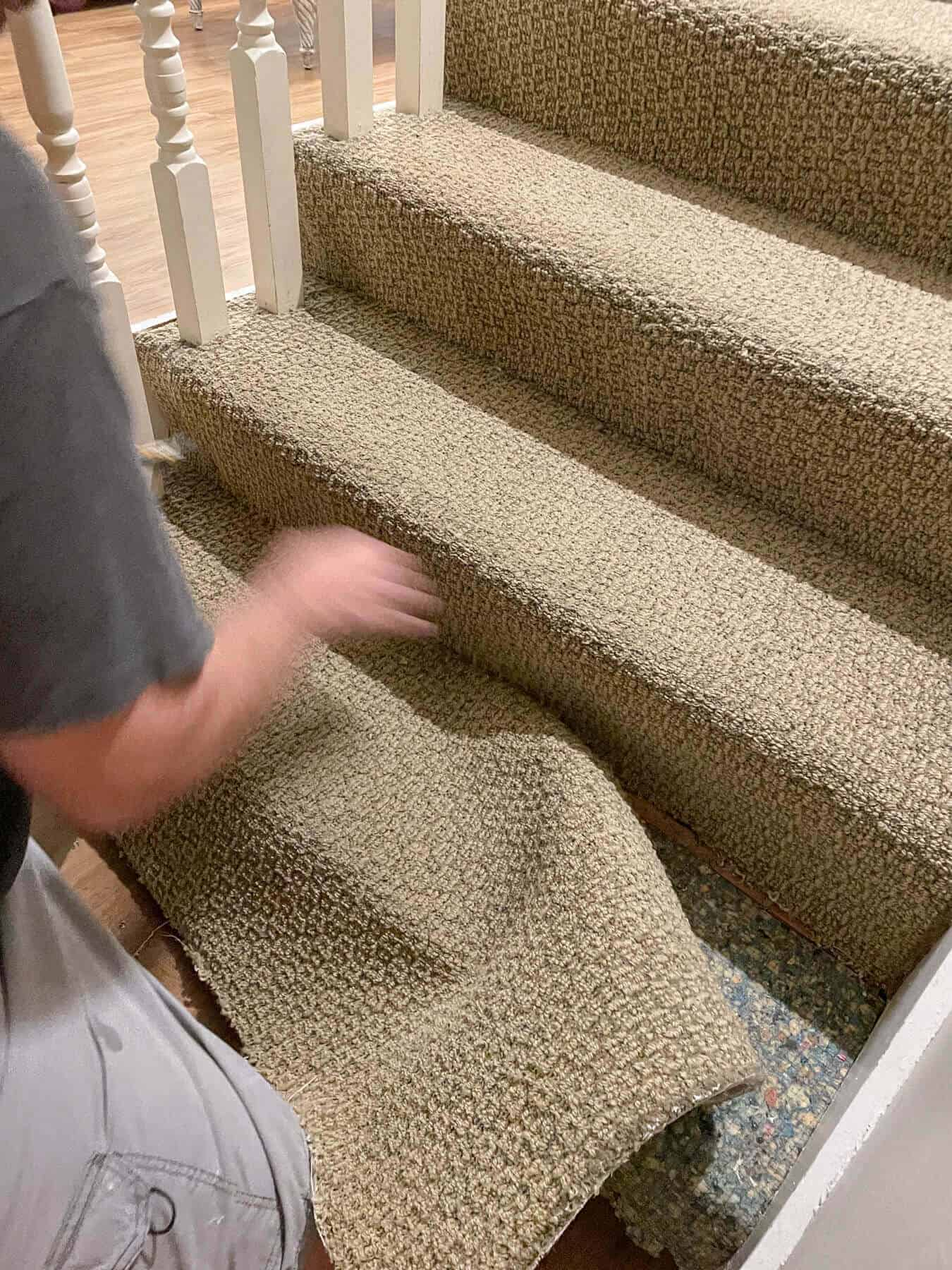 man ripping carpet off of basement stairs