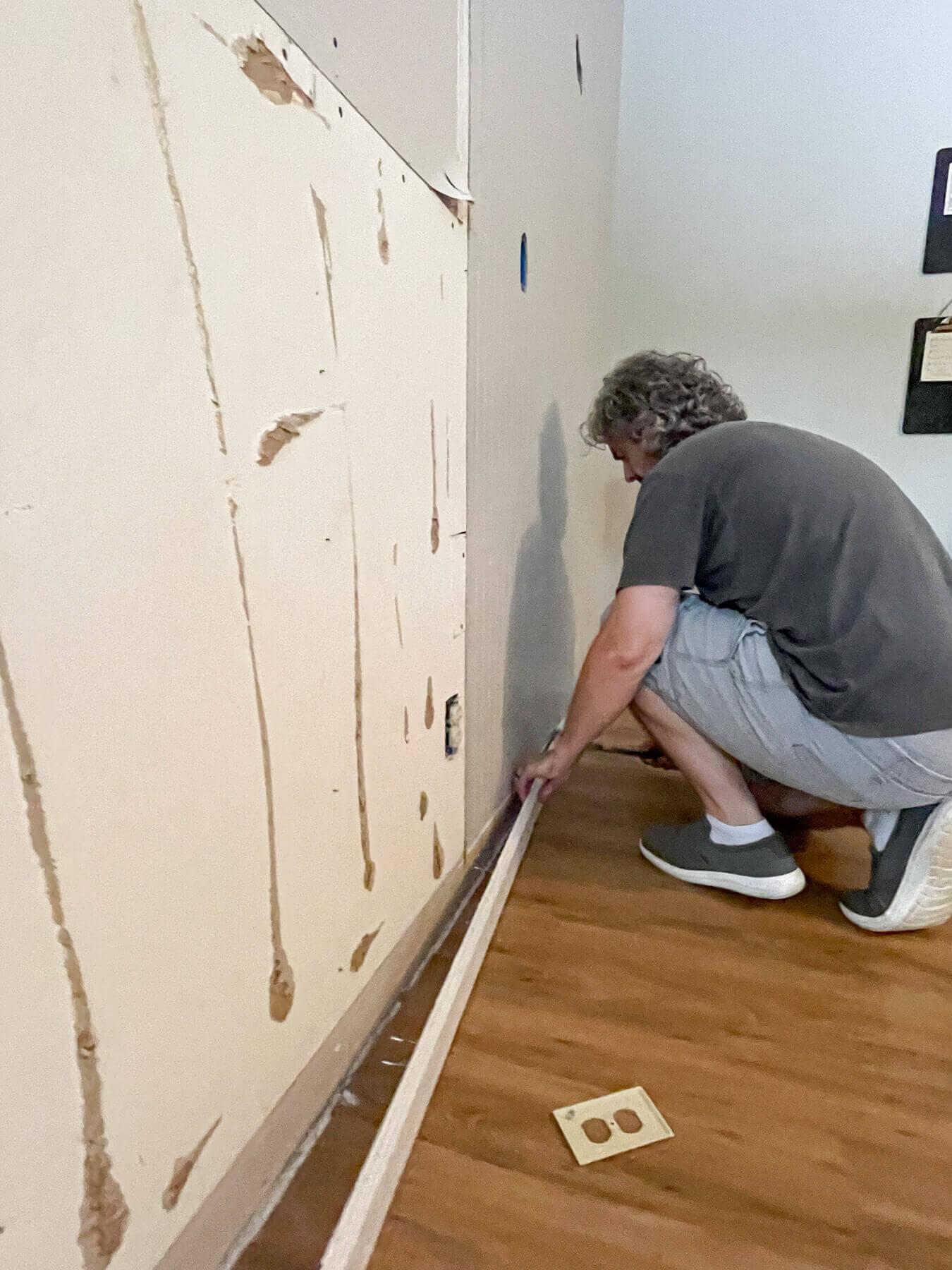 man removing baseboard.